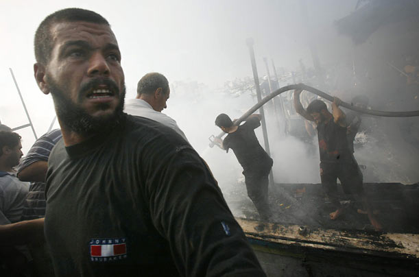 Palestinians extinguish the fire on a fishing boat after it was hit by Israeli naval fire at Gaza's seaport. The Israelis say the boat traveled