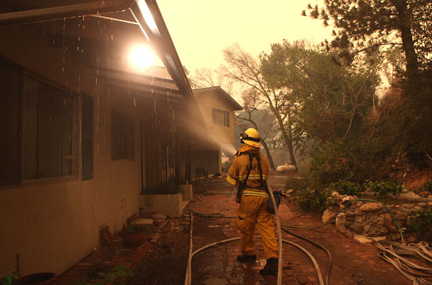 A Los Angeles City firefighter sprays foam fire retardant on a home in Tujunga, California, where the Station Fire has burned more than 120,000 acres.