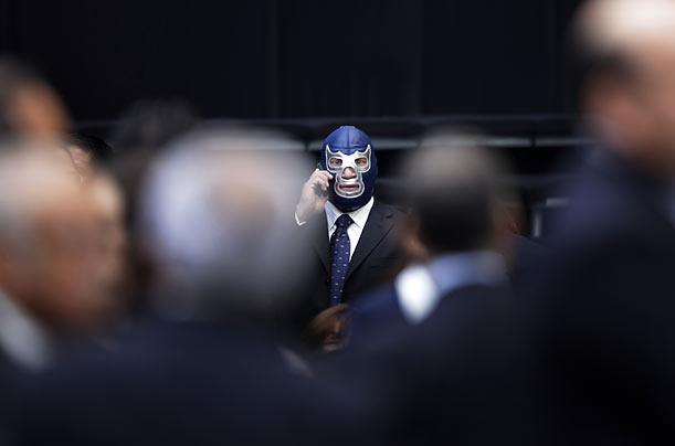Mexican wrestler Blue Demon speaks on a phone as he arrives for Mexico's President Felipe Calderon's third annual state of the nation address in Mexico City