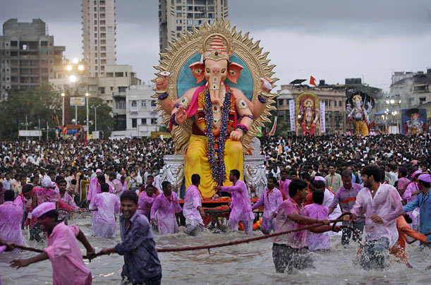 Policemen conIndian Hindus use ropes to pull a large statue of the elephant-headed deity Ganesh before immersing it in the Arabian Sea