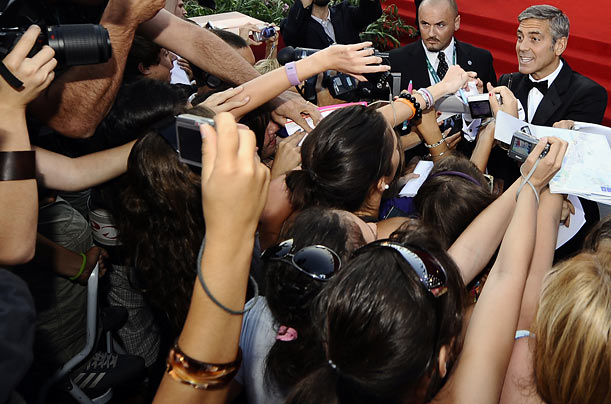 Actor George Clooney signs autographs as he arrives for the screening of The Men Who Stare at Goats at the Venice film festival.