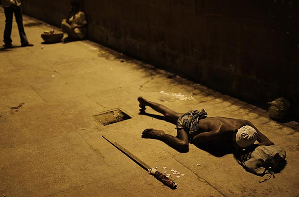 An Indian Muslim beggar lies on the ground in New Delhi
