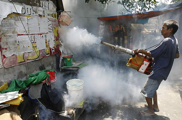 A government worker fumigates a slum community in Manila