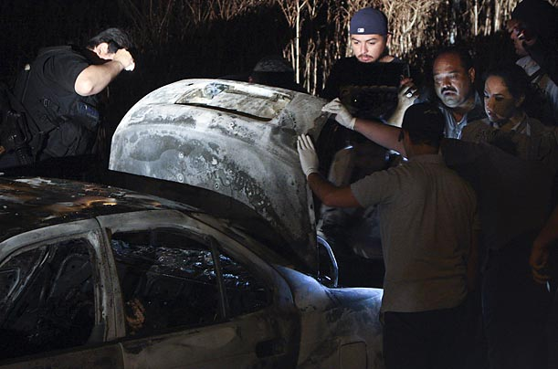 Police hold open the trunk of a car where six burned bodies were found in Tijuana, Mexico