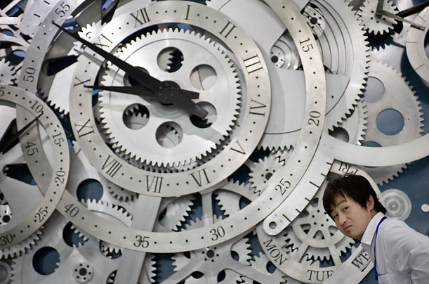 A man walks past the giant cogs of a watch on display at the newly opened China Science and Technology Museum in Beijing.