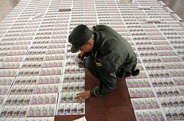 A police officer arranges seized counterfeit money during a presentation to the media in Medellin, Colombia.