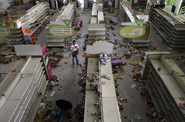 A cameraman takes pictures inside a looted supermarket in the El Pedregal neighborhood in Tegucigalpa, Honduras. The market was looted during clashes between governmehnt forces and supporters of ousted President Manuel Zelaya.