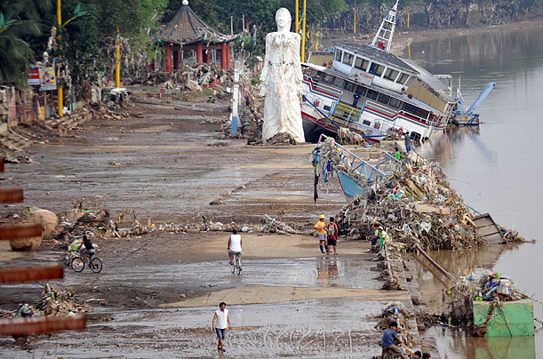 Residents walk past debris and a giant statue and restaurant boat swept away along the Marikina river outside Manila. Hundreds of thousands of exhausted Philippine flood