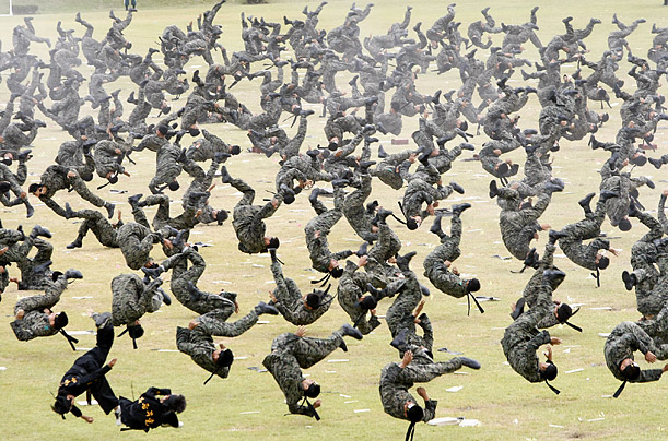 South Korean Special Army soldiers flip simultaneously as they demonstrate their martial arts skills during a rehearsal for the 61st anniversary of Armed Forces Day at the Gyeryong military