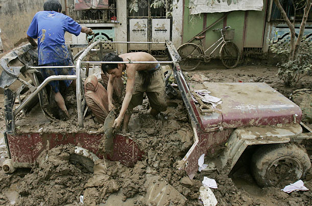 Residents clear mud off a vehicle in the storm-ravaged village of Rodriguez, in the Philippines.