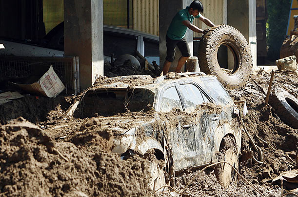 A resident retrieves a tire from a car shop that was destroyed by landslides at Puguis village in La Trinidad, The Philippines. The country is mounting major relief operations