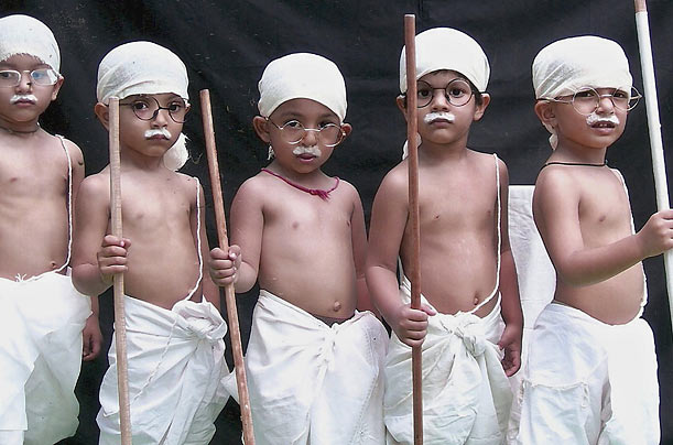Schoolchildren dressed as Mahatma Gandhi take part in a cultural event on the eve of Gandhi's 140th birthday in Bhopal, India.