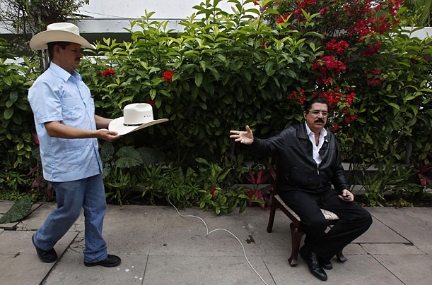 A supporter brings Honduras' ousted President Manuel Zelaya his hat before a press conference in the Brazilian embassy in Tegucigalpa.