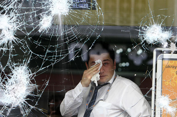 A man affected by tear gas wipes his eyes behind the broken windows of a shop during clashes between leftist protesters