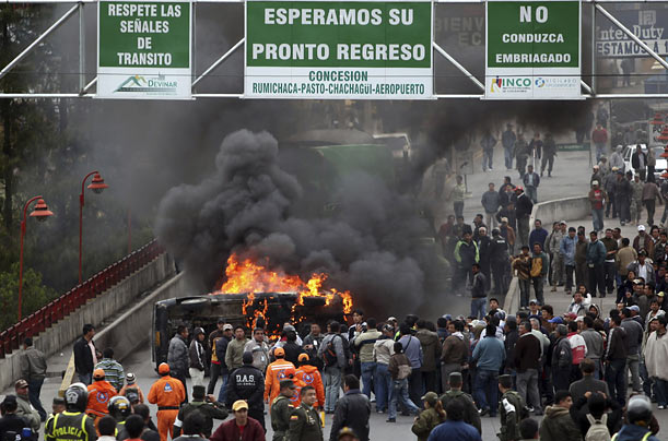 Colombian demonstrators burn a vehicle on a bridge connecting their country with Ecuador as foreign ministers from each country
