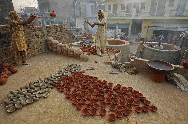 Potters prepare to bake earthen lamps for the upcoming festival of lights, or 'Diwali,' in New Delhi, India.