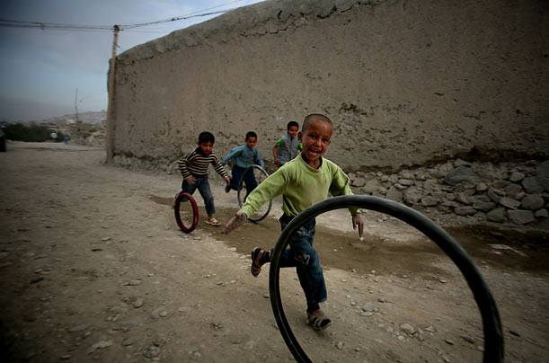 Young boys play with bicycle tires in Kabul, Afghanistan.