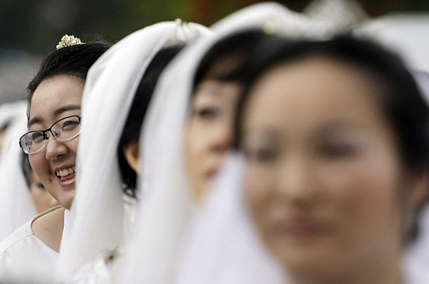 A bride smiles during the mass wedding ceremony arranged by the Rev. Sun Myung Moon in Asan, South Korea, that wedded more than 40,000