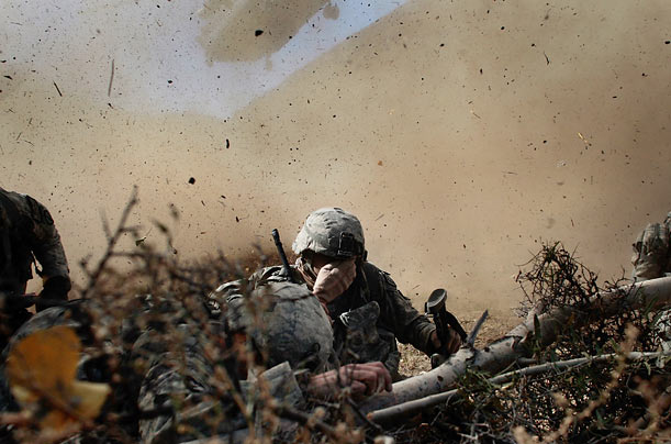 US Army soldiers shield their eyes from the powerful rotor wash of a Chinook cargo helicopter as they are picked up in