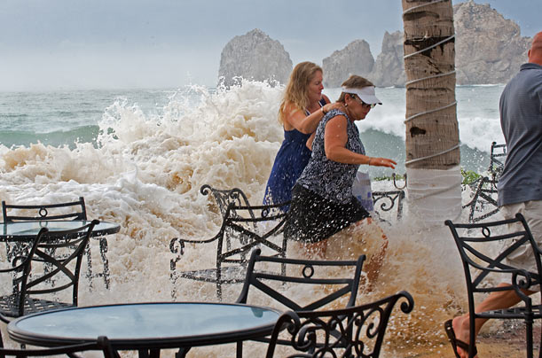 People flee the deck of a hotel in Cabo San Lucas, Mexico as large waves from Hurricane Rick overtake their perch.