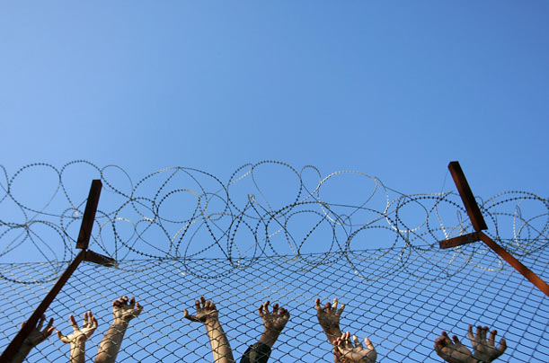 Immigrants protesting extreme overcrowding lean on a fence in their detention center in Lesvos, Greece.
