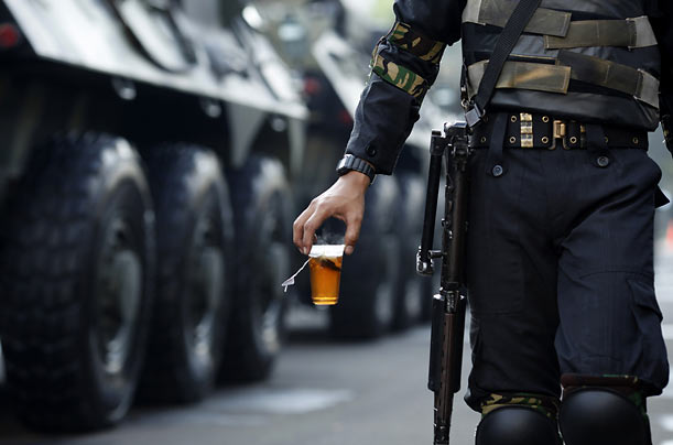An Indonesian soldier carries a cup of tea as he helps provide security during President Susilo Bambang Yudhoyono's inauguration in Jakarta.