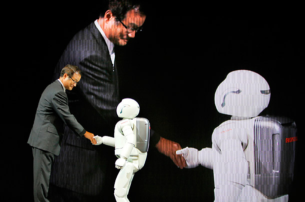Honda Motor President Takanobu Ito shakes hands with Asimo, a humanoid robot, at the 41st Tokyo Motor Show at Makuhari Messe in Makuhari, Japan.