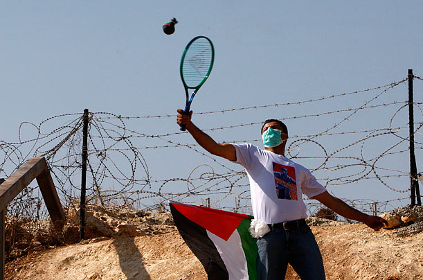 A Palestinian demonstrator uses a tennis racket to return an empty tear gas canister at Israeli soldiers during a protest against the controversial Israeli barrier in the West Bank village of Bilin near Ramallah.