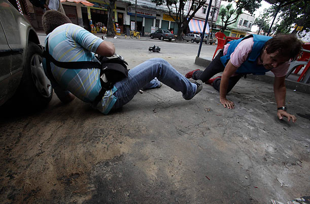 Journalists take cover during a police operation against drug dealers in the Vila Cruzeiro slum in Rio de Janeiro. As of Wednesday, 33 people have died since violence between rival gangs of drug traffickers erupted in Rio over the weekend.