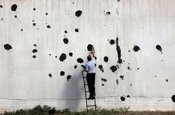 A Palestinian worker repairs a bullet-ridden wall damaged during the three-week offensive Israel launched last December, at a factory in the northern Gaza Strip.