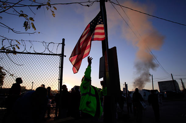 An officer for TWU Local 234 places an American flag on a pole as transport workers start a massive strike in Upper Darby, Pennsylvania