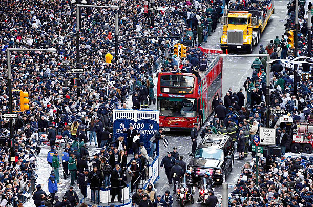 The victorious Bronx Bombers ride atop floats during a ticker-tape parade celebrating their 27th World Series championship.