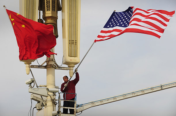 A worker hoists an American flag alongside its Chinese version on Tiananmen Square ahead of a visit by U.S. President Barack Obama.