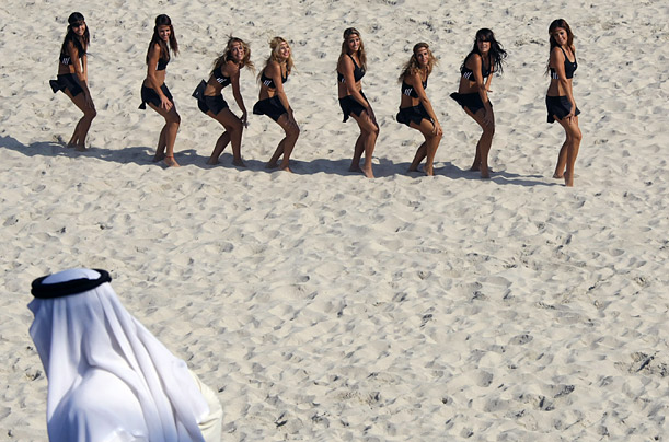 An Emirati man watches cheerleaders perform on the beach on the first day of the FIFA Beach Soccer World Cup at Jumeira, Dubai.