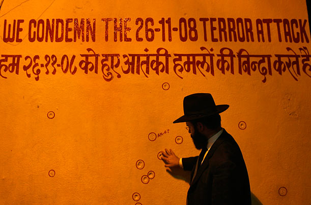 A rabbi touches a wall riddled with bullet holes in front of a Jewish religious headquarters in Mumbai after a multi