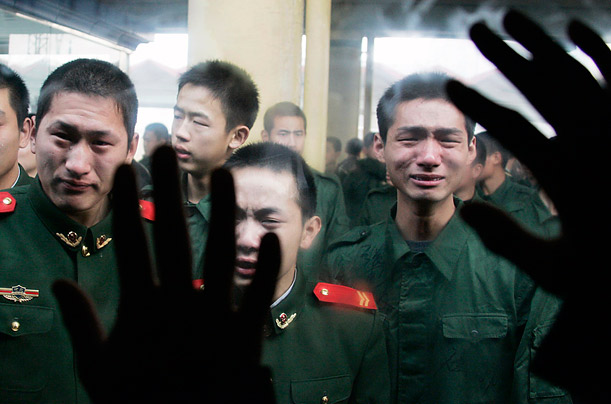 Former servicemen cry as they say goodbye to their fellow soldiers following the end of their army service term at a railway station in Shijiazhuang, Hebei province.