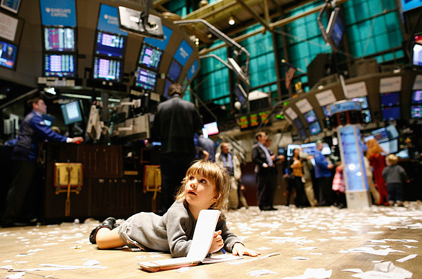 Gabriella Liloia lies on the floor of the New York Stock Exchange during Kid's Day, where children are allowed on to the trading floor during market hours.