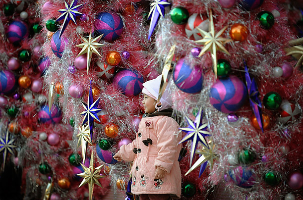 A child poses for a photo in front of a Christmas decoration outside a shopping mall in Beijing, China.