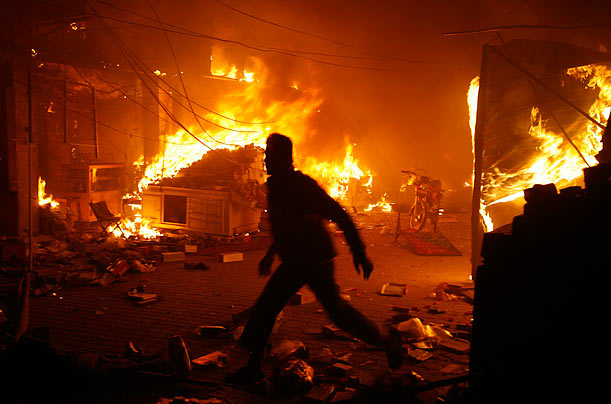 A man runs past a blaze after a suicide bomb explosion killed at least 12 people at a market in Lahore, Pakistan.