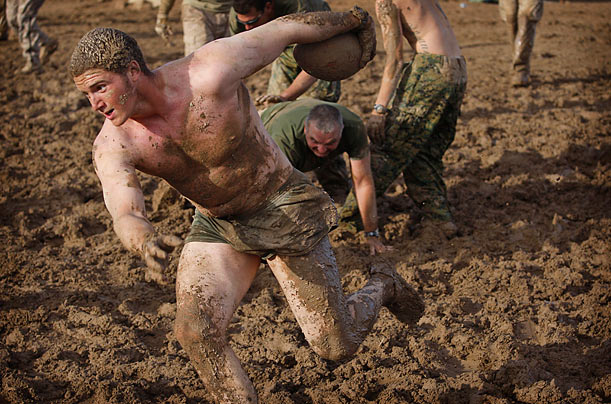 An American Army soldier runs during a game of mud football at a base in Khan Neshin, Helmand province, Afghanistan.