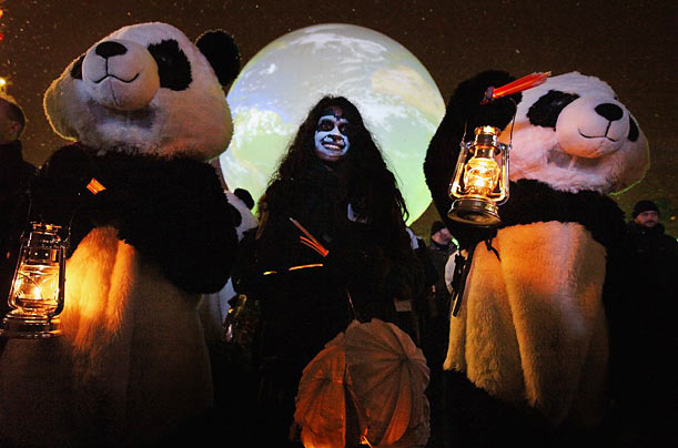 Two climate change protestors dressed as pandas attend an evening demonstration in Copenhagen.