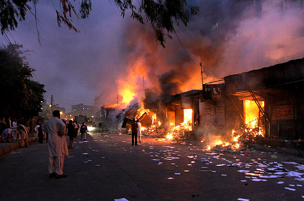 Local residents observe a market area in Karachi, Pakistan that was burned by angry protesters after a suicide attack on a Shi'ite Muslim mourning procession.