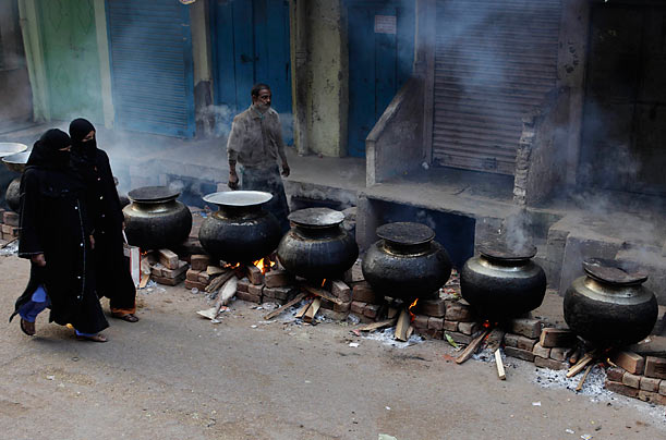 Indian Muslim women walk past free food being cooked streetside for the poor as part of the Ashura observation in Allahabad, India.