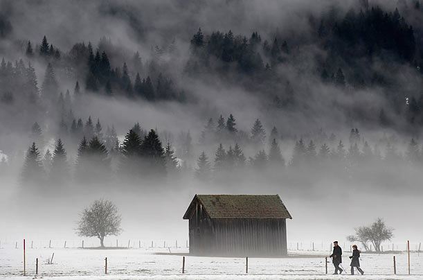Strollers pass a snow-covered meadow near the village of Oberstdorf in southern Germany.