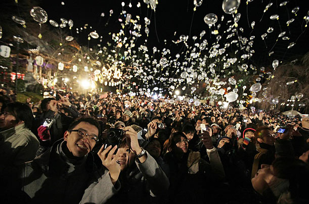 Crowds celebrate the New Year at the Zojoji Temple, in Tokyo, seconds after midnight.