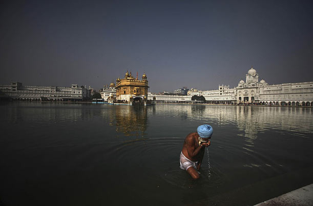 A Sikh devotee drinks water from the holy pond after taking a dip, on the eve of the birthday of the 17th century guru Gobind