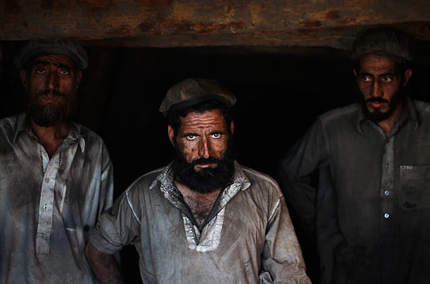 Pakistani laborers take a break from working at a coal mine in Khewra, Pakistan.