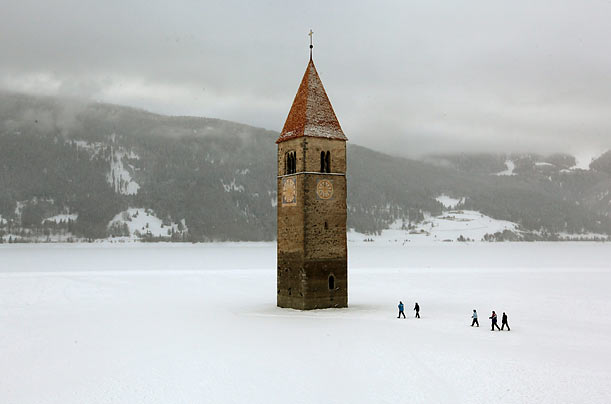 People walk on the frozen Lake Reschen reservoir toward the former church tower of Graun in northern Italy. This village was destroyed
