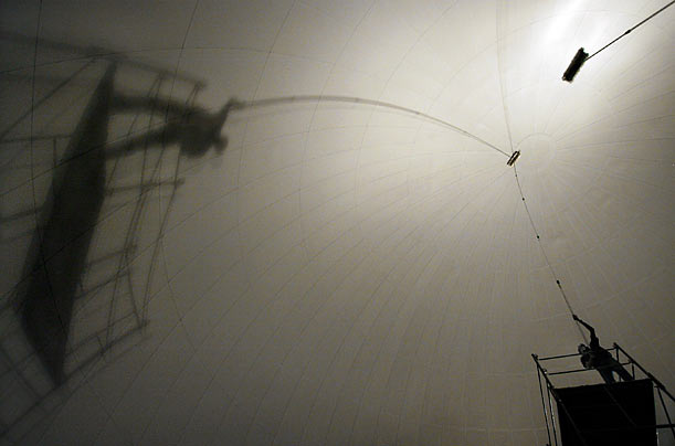 A worker cleans an IMAX screen at the Science Museum of Virginia in Richmond. The brush he is using is attached to a 30-foot-long aluminum pole.
