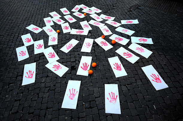 Showing solidarity with Italy's besieged migrant worker population, members of Italian anti-racism associations set up an installation of orange painted hands and fruit in Rome.